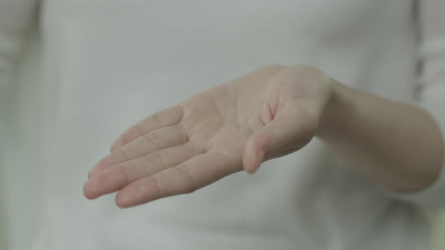 view of woman showing a palm and wearing a white cloth - palm stock videos & royalty-free footage