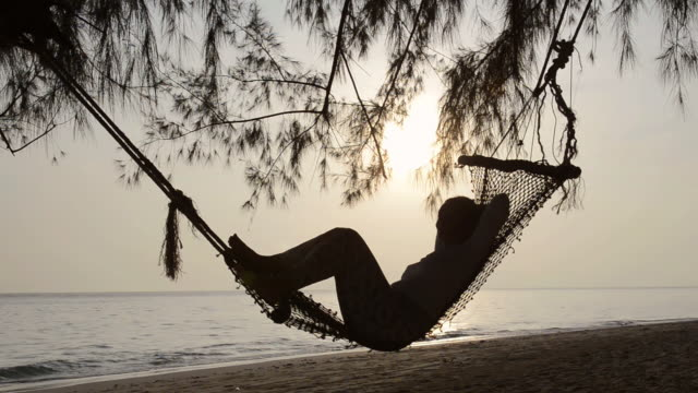 vídeos de stock, filmes e b-roll de ms view of woman swing in hammock at beach at sunrise, hat chao mai marine national park / ko kradan, trang, thailand - rede de dormir