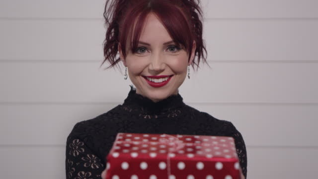 View of woman with red hair smiling as she hands you a gift