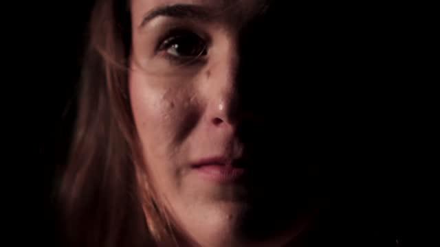view of woman's face in darkness - endast unga kvinnor bildbanksvideor och videomaterial från bakom kulisserna