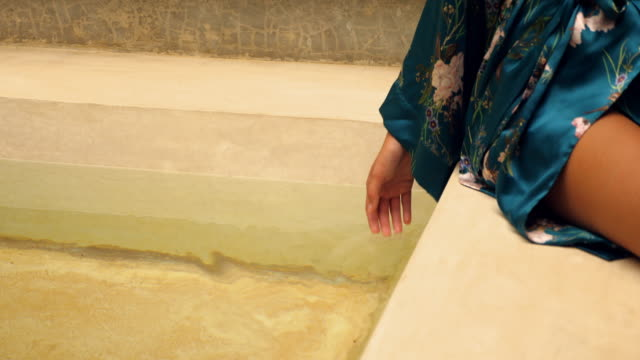 CU View of womans hand testing water temperature in bathtub