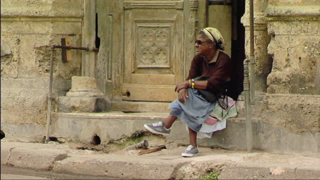 ws view of women sitting on porch and watching traffic / havana, cuba - front stoop stock videos and b-roll footage