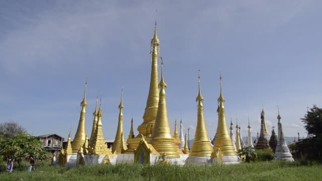WS View of Women walking in front of golden Stupa temple / Ywama, Inle Lake, Shan State, Myanmar