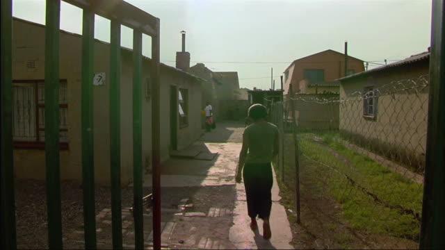 vídeos de stock e filmes b-roll de ws view of women walking into small home area / south africa - mill