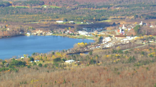 WS AERIAL PAN ZI View of Wooded area with autumn color at Island Pond / Vermont, United States