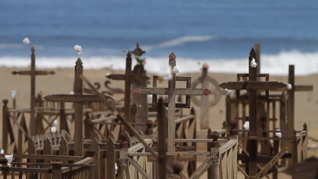 MS View of Wooden crosses with white flowers hanging in front of sea waves / Gatico, Atacama desert, Chile