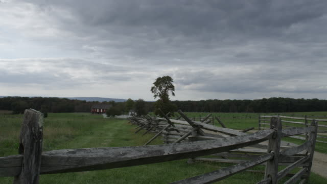 ws view of wooden fence and field, with dark clouds in sky / gettysburg, pennsylvania, united states - gettysburg stock videos & royalty-free footage
