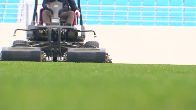vidéos et rushes de view of worker mowing the soccer turf in soccer stadium, daegu, south korea - herbe