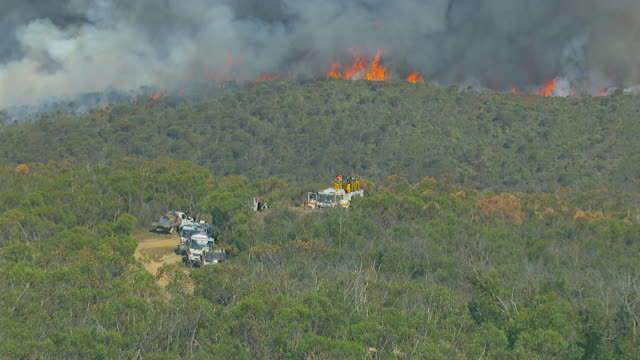 ms aerial zi slo mo view of worker standing at burning wooded area / adelaide, south australia, australia - australia stock videos & royalty-free footage