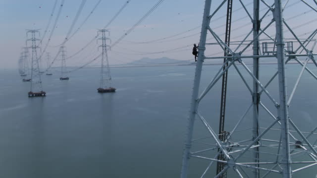 view of worker to climb up the high-voltage tower in sihwaho, ansan - 塔 個影片檔及 b 捲影像
