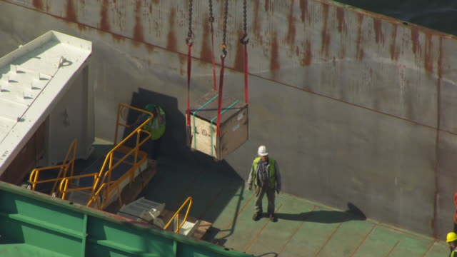 vidéos et rushes de ms aerial ds view of workers load box into barge using cranes / milwaukee, wisconsin, united states  - débardeur