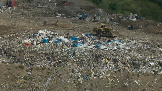 View of workers moving trash in landfill in Mexico City.
