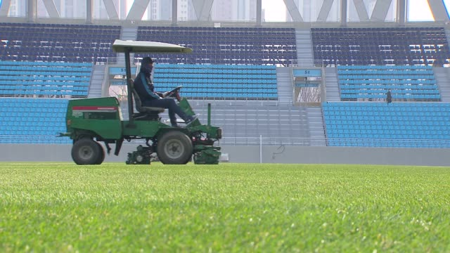 vídeos de stock e filmes b-roll de view of workers mowing the soccer turf in soccer stadium, daegu, south korea - campo de futebol