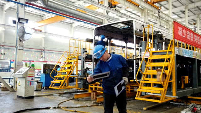 view of workers working in bus factory - automobilindustrie stock-videos und b-roll-filmmaterial