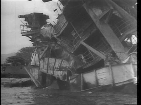 view of wreckage from uss utah the ship capsized in the harbor / pan of wreck with small boats and guards / uss oklahoma capsized showing propeller /... - anno 1941 video stock e b–roll