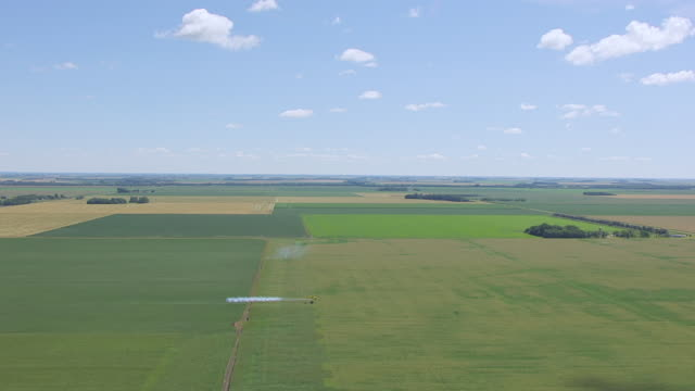 ws aerial ts view of yellow airplane crop dusting field / wahpeton, north dakota, united states - spraying stock videos & royalty-free footage
