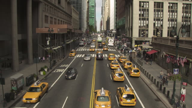 View of yellow taxis and other vehicles passing under a bridge crossing a wide Manhattan street, New York City, USA.