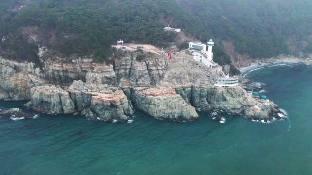 view of yeongdo lighthouse in taejongdae park(the southernmost tip of yeongdo-gu district), busan - crag stock videos and b-roll footage