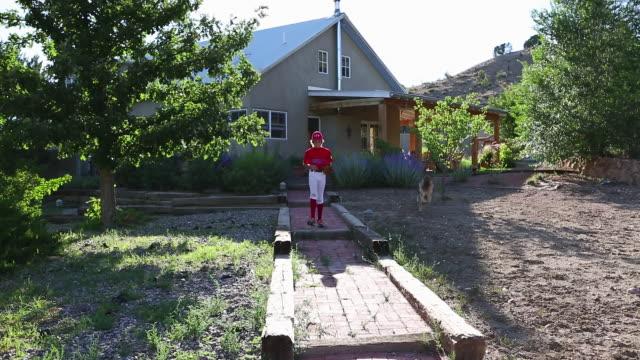 vídeos y material grabado en eventos de stock de ws view of young baseball player leaving his home with dog / santa fe, new mexico, united states - gorra de béisbol