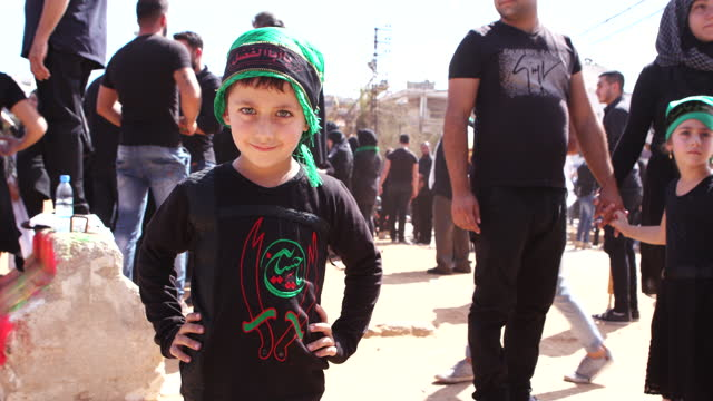 view of young boy with green eyes wearing an ashura headband and tshirt looking into the camera he is at the ashura commemoration organised by... - hair accessory stock videos & royalty-free footage
