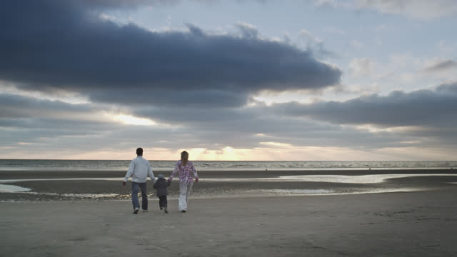 WS View of young couple and child at beach, walking towards ocean and lifting up young child while doing so / St. Peter Ording, Schleswig Holstein, Germany