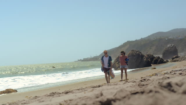 ws view of young couple at beach walking towards / pacific palisades, california, united states  - asciugamano video stock e b–roll