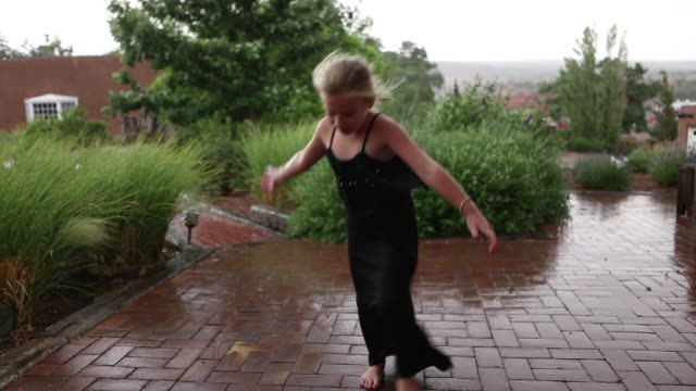 ws view of young girl hula hooping in rain / lamy, new mexico, united states - lamy new mexico stock videos and b-roll footage