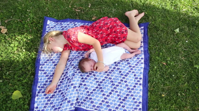 ws view of young girl laying with her baby brother outside / lamy, new mexico, united states - auf der seite liegen stock-videos und b-roll-filmmaterial