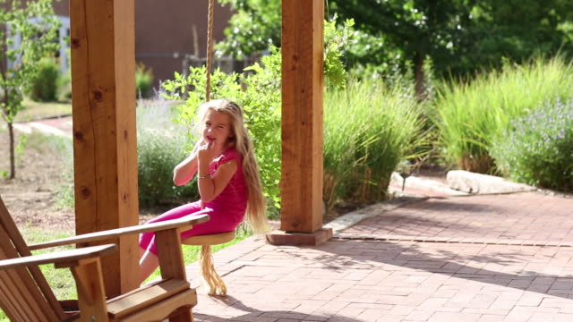 WS View of young girl playing on swing on her porch / Lamy, New Mexico, United States