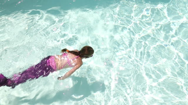 ws view of young girl pretending to be mermaid in pool / lamy, new mexico, united states - swimming costume stock videos and b-roll footage