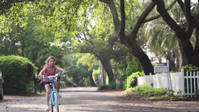 WS View of young girl riding her bike near home / St Simon's Island, Georgia, United States
