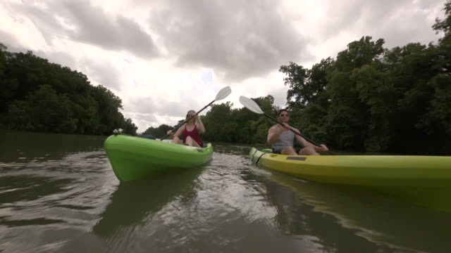 WS TS View of young man and woman kayaking towards in tranquil water / Austin, Texas, United States