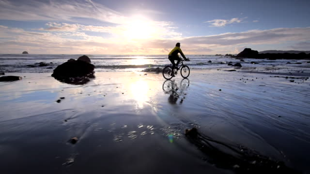 ws ts view of young man mountain biking on beach / shore acres state park, oregon, united states - oregon us state stock videos & royalty-free footage