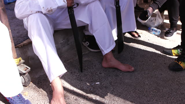 view of young men and boys sitting on the pavement in exhaustion after performing tatbir during the ashura commemorations in nabatieh. tatbir is an... - pavement点の映像素材/bロール