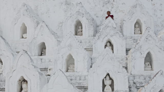 WS View of young monk climbing down white temple steps with Buddha statues inside them  / Mandalay, Mandalay Division, Myanmar