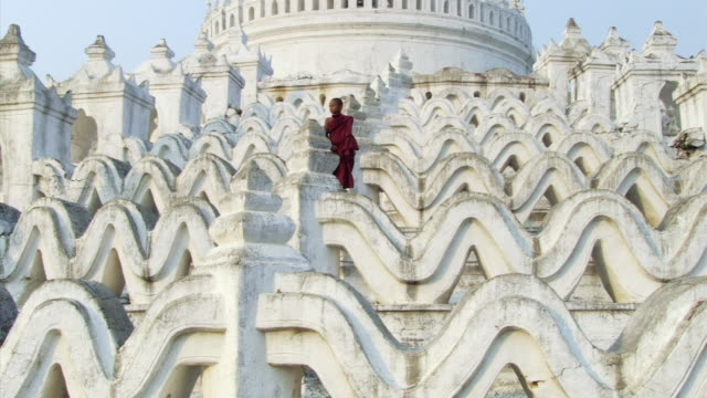 WS View of young monk standing calmly on huge white temple steps  / Mandalay, Mandalay Division, Myanmar