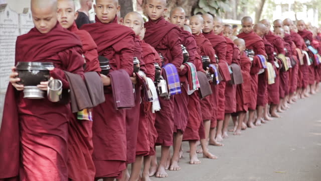 ws view of young monks waiting in line for their meal, carrying marmites (seen from side)  / mandalay, mandalay division, myanmar - people in a row stock videos and b-roll footage