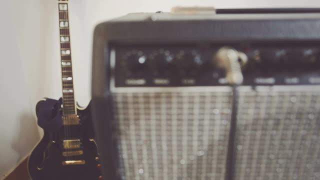 auf der verstärker knobs, steckdosen und electric guitar - moderne rockmusik stock-videos und b-roll-filmmaterial