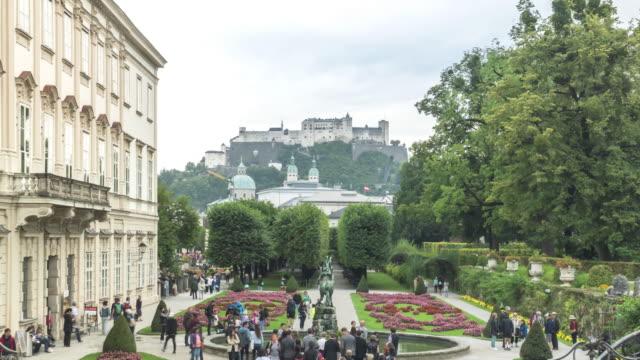 オーストリアのザルツブルクにある歴史的な要塞を持つ有名なミラベル庭園のtlビューが、日は雨が降っています - オーストリア文化点の映像素材/bロール