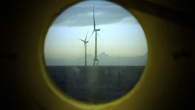 view on offshore wind-turbine, windfarm true round window from sailing vessel in sunrise. dramatic sky. - turbine stock videos & royalty-free footage