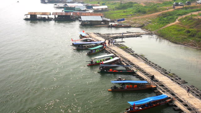view on pier with traditional long tailed boats - longtail boat stock videos & royalty-free footage