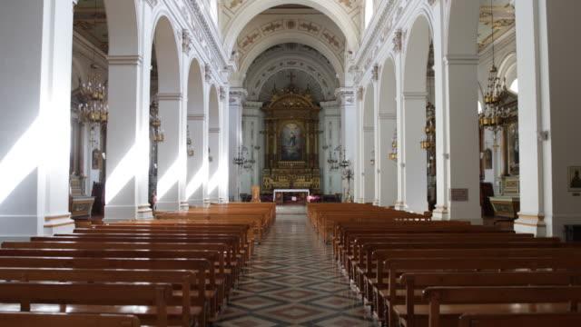 vídeos de stock e filmes b-roll de view on the interior of the baroque church iglesia de san ignacio in santiago de chile which was built 1872 in front the wooden benches to both sides... - chile
