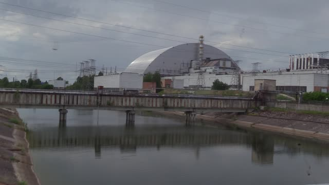 stockvideo's en b-roll-footage met view on the protective shelter over the remains of the nuclear reactor unit 4 at the chernobyl nuclear power plant during a press tour of the... - kernramp van tsjernobyl