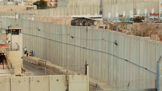 vídeos de stock e filmes b-roll de a view onto the israeli side of the west bank barrier seen from above in bethlehem, palestine. - muro circundante
