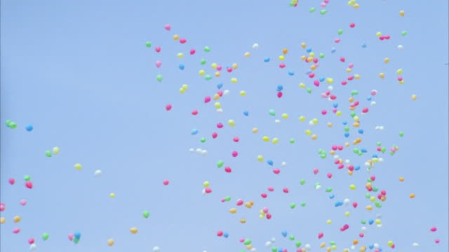 MS ZI ZO View or Hundreds of small multi-colored helium filled balloons as they rise into sky.