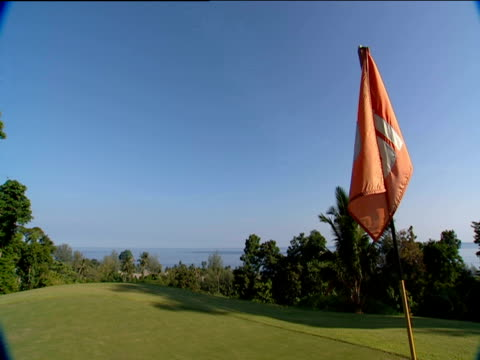 view out to sea from tropical golf course with golf flag in foreground malaysia - golf flag stock videos & royalty-free footage
