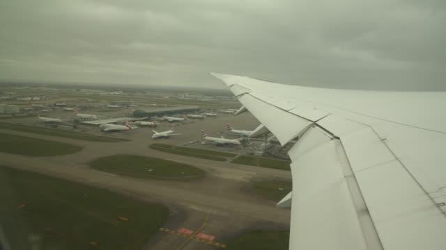 view outside an airplane window of heathrow airport - flugzeugflügel stock-videos und b-roll-filmmaterial