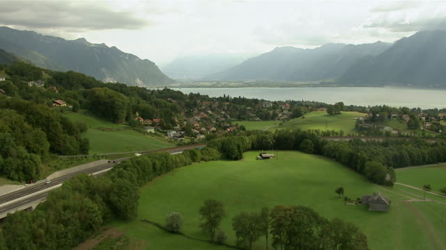 WS AERIAL View over A12 Highway and village of St Legier, Blonay, Chailly with Chateau du Chatelard. With Lake Geneva and Chablais mountains / St. Legier, Switzerland