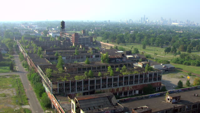 ws aerial view over abandoned packard automotive plant to reveal downtown in distance / detroit, michigan, united states - bad condition stock videos & royalty-free footage