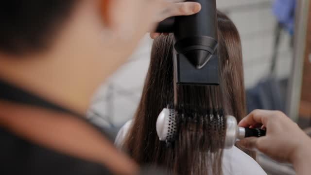 vidéos et rushes de vue sur le jeune homme asiatique barber comme l'épaule du coiffeur faisant service cheveux raides de belles cheveux bruns de la femme caucasienne en utilisant un sèche-cheveux, peigne à cheveux à la boutique de salon, concept de la vie d'un travail - brown hair